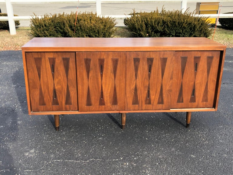 Mid-Century Modern walnut credenza. Unique two-toned harlequin pattern on four front doors. Four front doors slide on tracks to reveal interior shelving. Solid well built piece with 6 legs. It is rare to have two center support legs. So this is a