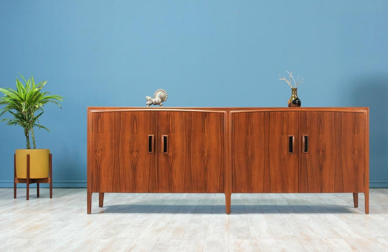 Stunning credenza manufactured circa 1950's. This credenza features an elegant walnut wood case with with ample storage. The four pull-open front doors feature a slightly arched top, sculpted walnut pulls and panels of magnificent grain details.