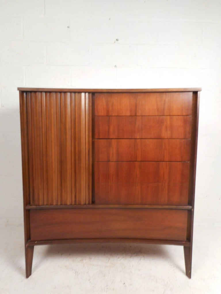 This beautiful vintage modern dresser features a unique curved front with a large hidden drawer on the bottom. There is plenty of room for storage within its nine hefty drawers with four of them hidden by a cabinet door. Sleek design with sculpted
