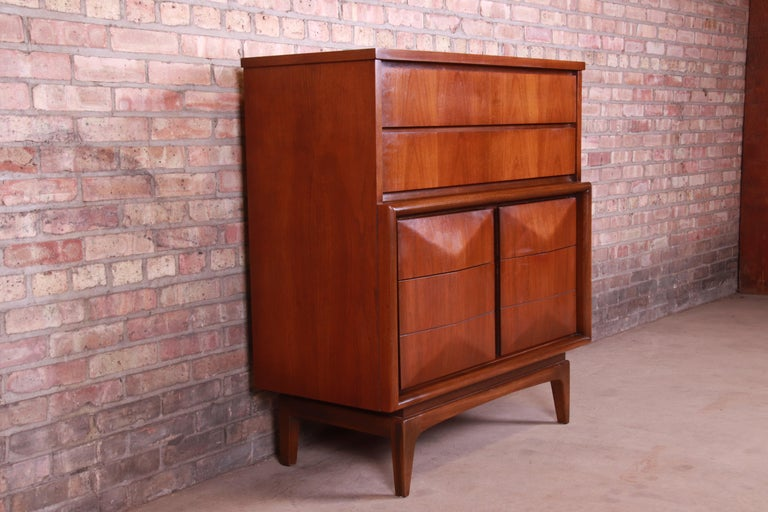 A stunning Mid-Century Modern sculpted walnut diamond front six-drawer highboy dresser  In the manner of Vladimir Kagan  By United Furniture Co.  USA, 1960s  Measures: 40
