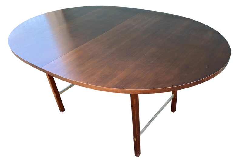 A Mid-Century Modern walnut extension dining table designed by Paul McCobb for Calvin Furniture. The table features dark walnut wood grain and aluminum stretchers. The table is in original vintage condition. Great Design.