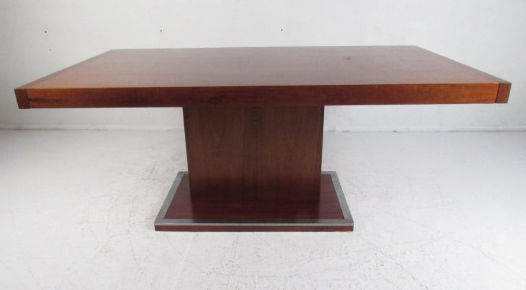 This stunning vintage modern dining table features a unique pedestal base with metal trim wrapped around the edges. The Art Deco style design, clean lines, and elegant walnut wood grain shows quality craftsmanship. This attractive mid-century dining