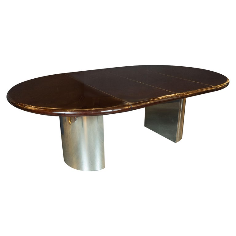 This magnificent Mid-Century Modern dining table was realized by the esteemed American maker, Directional in the United States, circa 1970. It features two demilune form curved feet in polished chrome that support a circular walnut tabletop. The