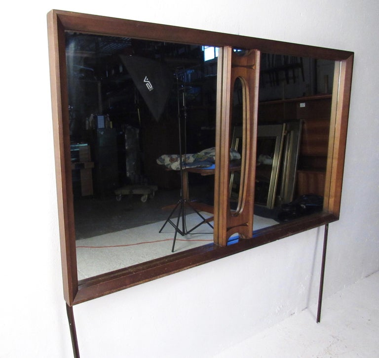 This stylish Mid-Century Modern mirror boasts sculpted walnut trim and makes an impressive mirror for use on top of a bedroom dresser or updated to use as a hanging wall mirror. Please confirm item location (NY or NJ).