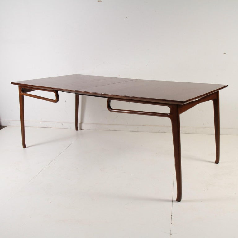A rather rare 1950s vintage dining table with two leaves that was originally a pickled finish with black airbrushed accents. This great piece has been updated and refinished to display its walnut grain and to better highlight its Italian-influenced