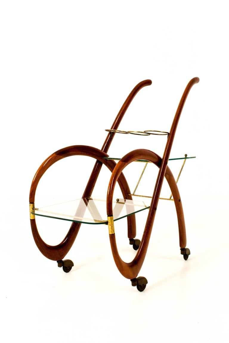 Magnificent Mid-Century Modern bar cart or trolley. Design by Gaetano Pizzi. Striking Italian design from the 1950s. Walnut frame with two original glass trays and brass wheels. The most elegant bar cart ever designed. In good original