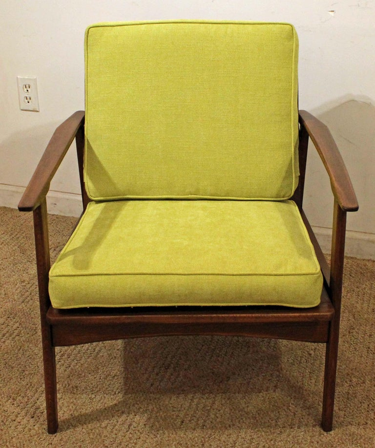 Offered is a Mid-Century Modern open-arm lounge chair. This piece is made of walnut and has been reupholstered with 'citron' fabric. The chair comes apart for easy shipping and storage. It has been reupholstered and is not