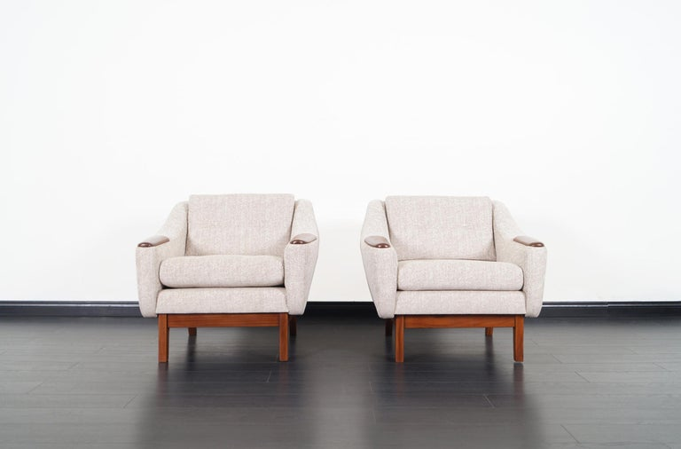 Fabulous pair of Mid-Century Modern lounge chairs. Each chair features a solid thick walnut sculptural armrests and a sturdy base.