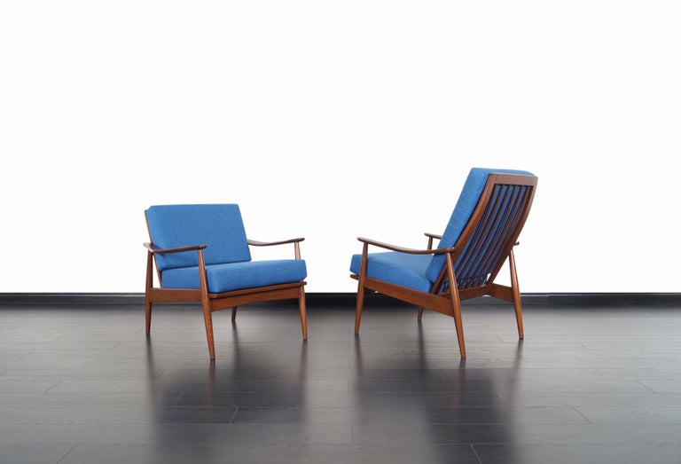 Fabulous pair of Mid-Century Modern lounge chairs, manufactured in the United States. These chairs features a solid walnut stained oak frames with sculptural armrests and slatted backrests. The perfectly symmetrical proportions and clean lines on