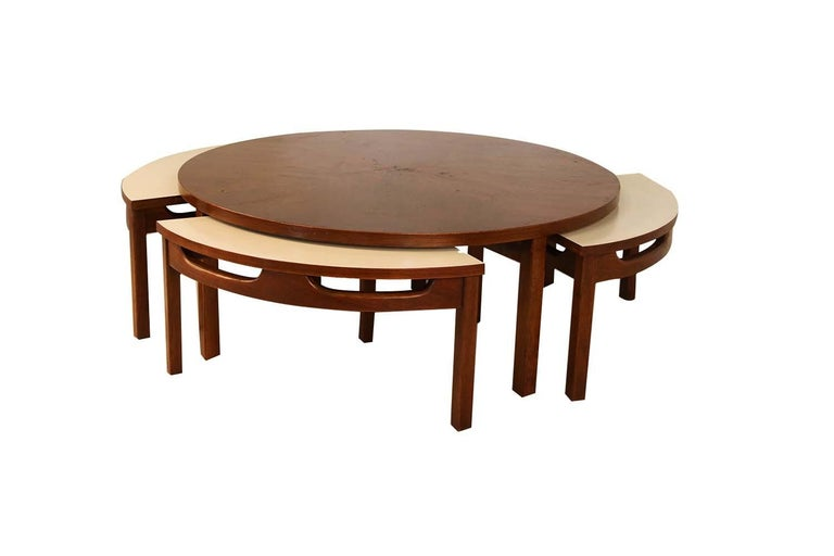 This impressive Mid-Century Modern walnut round coffee table includes four white laminate/walnut nesting tables. This rare coffee table features a book-matched heartwood walnut veneer top resting on four strong angular walnut legs. The four pie