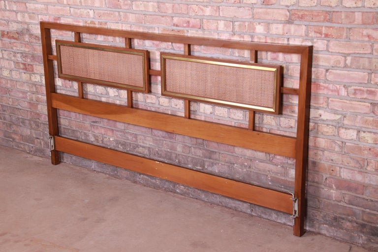 A gorgeous Mid-Century Modern king size headboard  USA, circa 1960s  Walnut, with inset rattan panels and brass trim.  Measures: 78