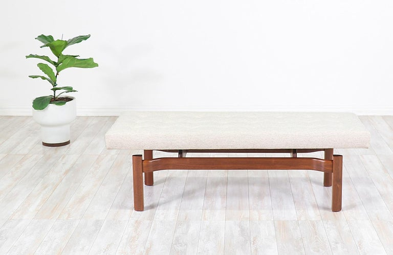 Sculpted Mid-Century Modern bench designed and manufactured in the United States, circa 1950s. This elegantly carved bench features a solid walnut wood base with a long cushion held by two perpendicular stretchers in a way that makes it seem like a