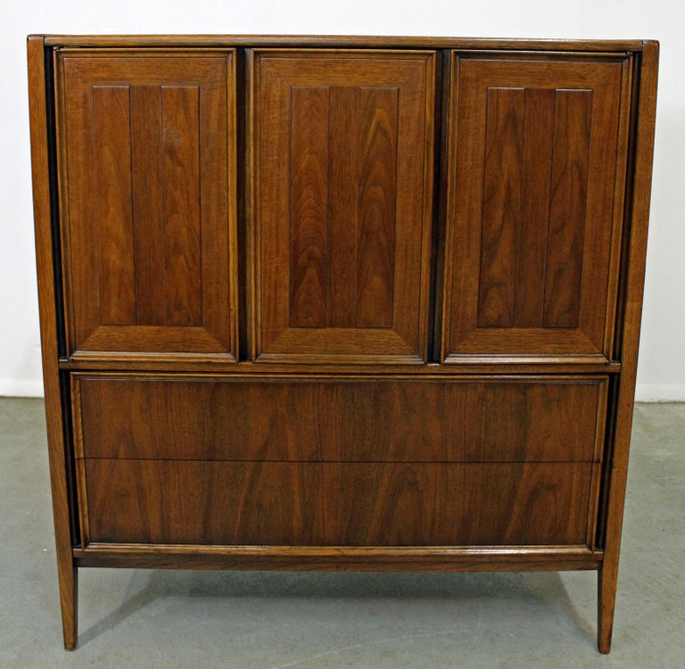 Offered is a Mid-Century Modern walnut tall chest or armoire. Includes five drawers altogether with three doors on top. Top drawer has a divider. It is in good condition, shows some wear (age wear, surface scratches/scuff marks- see photos), but