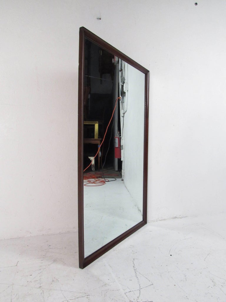 A beautiful vintage modern mirror with a dark walnut frame. Sleek design with a rectangular shape and bevelled edges. This stylish midcentury piece looks great as a wall mirror or attached to the back of a dresser. Please confirm item location (NY