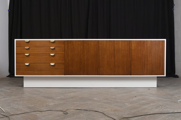 This large Mid-Century Modern credenza has been professionally restored, stained in walnut and white combination, and has a newly lacquered finish. The credenza features four top drawers with dual sold brass handles, two center doors with two