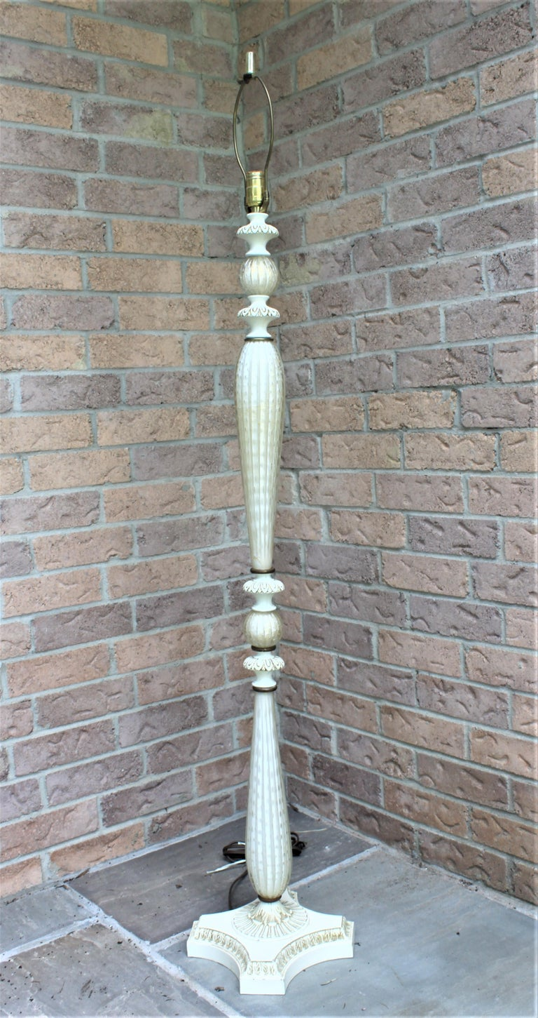 This Mid-Century Modern art glass floor lamp is done with white art glass with controlled bubbles and gold flecks or aventurine with a tapered and ribbed body and accented with an off white painted metal base with brass rings which accent both the