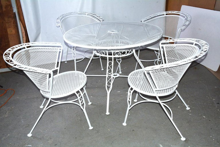 Five-piece outdoor dining set includes a dining table and four armchairs. The dining table features a Classic design with Classic diamond mesh wire top with an umbrella stand in the center. The armchairs are very comfortable with a curved barrel