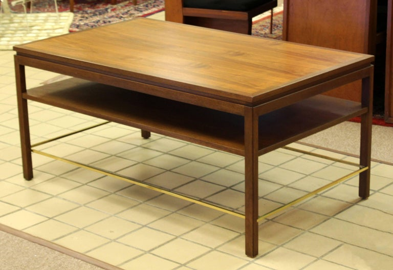 For your consideration is a phenomenal, walnut and brass, two-tier coffee cocktail occasional table by Edward Wormley for Dunbar, circa the 1950s. In excellent condition. The dimensions are 48