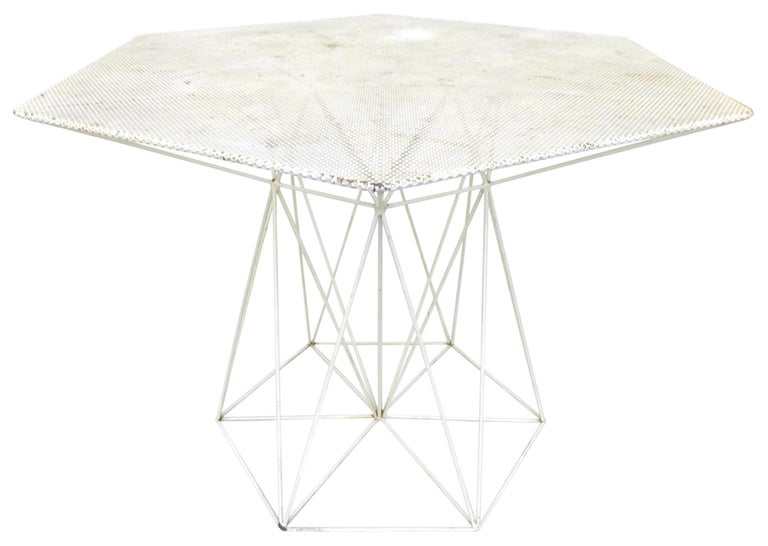 An outstanding, modernist, wrought iron, outdoor set of a table and four chairs. Highly unusual and alluring geometric forms, all with an impressive array of especially angular cross-stretchers and thoroughly perforated surfaces. Seemingly original
