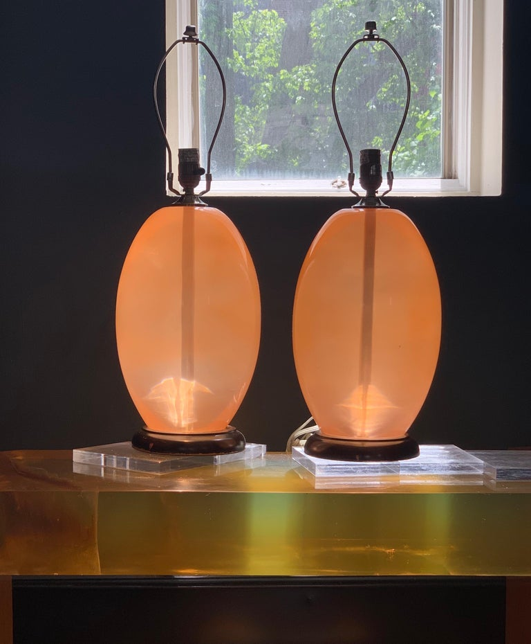 Midcentury monumental ostrich-egg pink Lucite or Resin or Acrylic modern sculptural table lamp. Wood base. Listing is for single lamp. Two available.