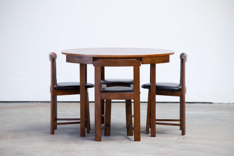 Scandinavian Modern designed, rare dining table and four chairs. The table accommodates four chairs neatly tucked around its outer rim. It has been loving restored and polished.