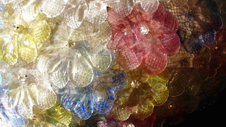This amazing flower basket is made of dozen of precious Murano flowers glasses. Pink , Yellow , Blu , Light blu  and  Ice color handblown flowers.  Available a pair and also a pair of extraordinary sconces. Six E 14 light bulbs  with 4 Watt lights.