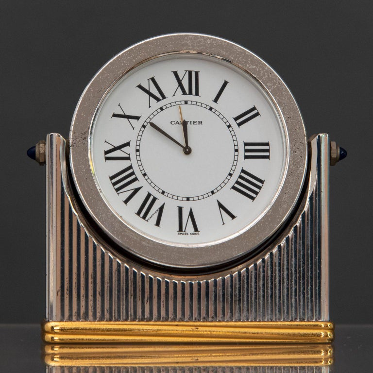 Table alarm clock, steel and brass tilting frame, white dial with Roman hour markers, quartz movement and two cabochon sapphires on the sides.