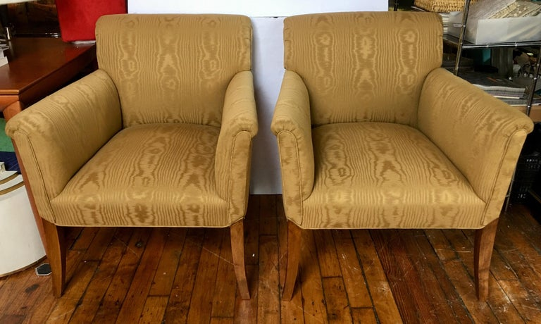 Perfectly proportioned pair of classic gold moire upholstered tight-back arm accent chairs featuring gently flared arms and legs. These generously sized pair of lounge chairs have subtle rolled arms and backs and beautifully curved walnut wood legs.