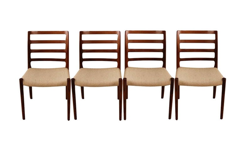 An absolutely stunning set of four midcentury Danish modern rosewood dining chairs model 85 designed by Niels Otto Moller for J.L. Møllers Møbelfabrik in Denmark. Makers stamp (Moller Models made in Denmark) underneath seats. These gorgeous chairs