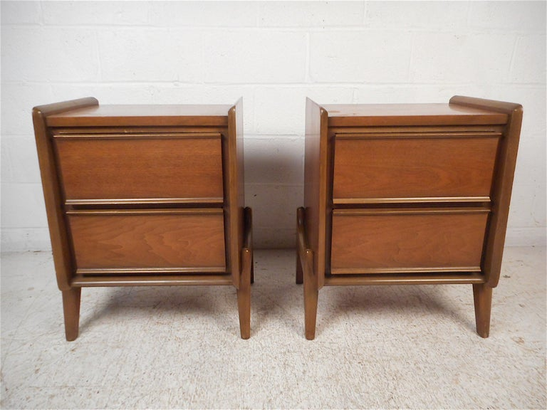 Stylish pair of midcentury nightstands by Grand Rapids Furniture Company. Sleek design with raised edges on the tabletops and sculpted legs. Two spacious drawers on either piece offer ample storage space. This pair is sure to prove a great addition