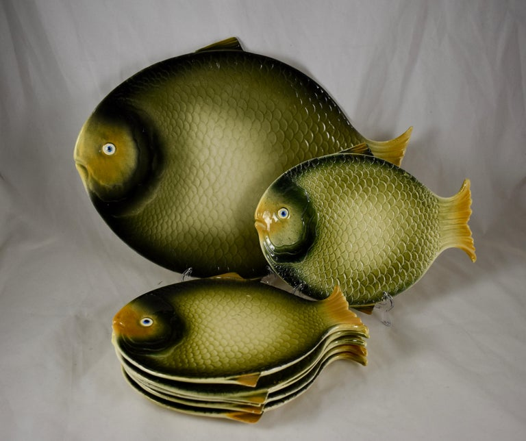 From the Barrettoni già Antonibon pottery in Nove, Northern Italy, a Mid-Century Modern Era earthenware fish service consisting of a large serving platter and six individual plates. Each piece is formed as a fish with dimensional mold work of
