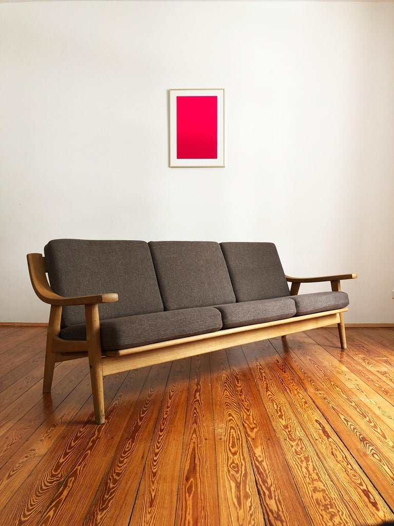 Sofa designed by Hans J. Wegner and produced by GETAMA, made out of solid oakwood. The Sofa shows best Danish quality craftsmanship. It comes with renewed box spring cushions.