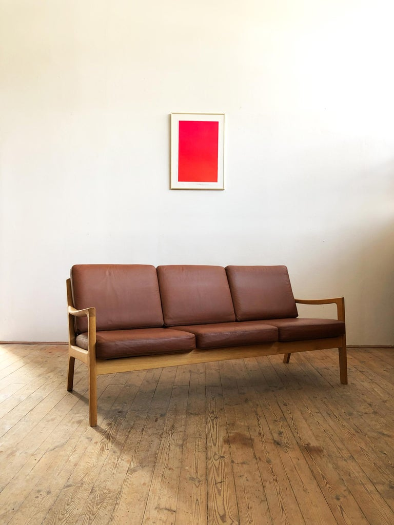 This shapely and comfortable sofa was designed by Ole Wanscher for Poul Jeppesens Møbelfabrik. This piece comes in a very rare version made of oakwood with foam cushions and a leather cover.