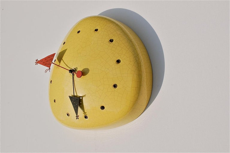 Midcentury ceramic wall clock that is more than likely a one-off creation made by hand (unsigned). The design is highly imaginative and rather quirky. The hollow, slightly domed ceramic body is decorated in a bright yellow crackle glaze. The hours