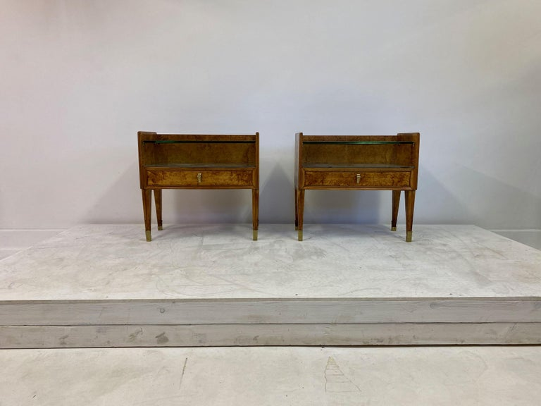 Pair of bedside tables  Burl wood  Striking grain  Grey glass top which can be removed to show grain underneath (see photos)  Thick glass shelf  Brass feet  Brass handles  Quality brass details  Italy 1950s.