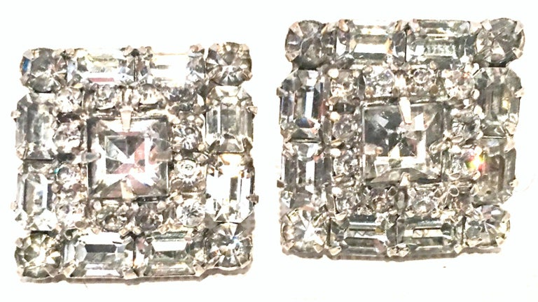 Mid-Century Art Deco Silver Pot Metal Prong Set Austrian Crystal Clear Rhinestone earrings. These brilliant and dimensional  clip style earrings feature brilliant cut and faceted baguette and round crystal rhinestones with a central square cut