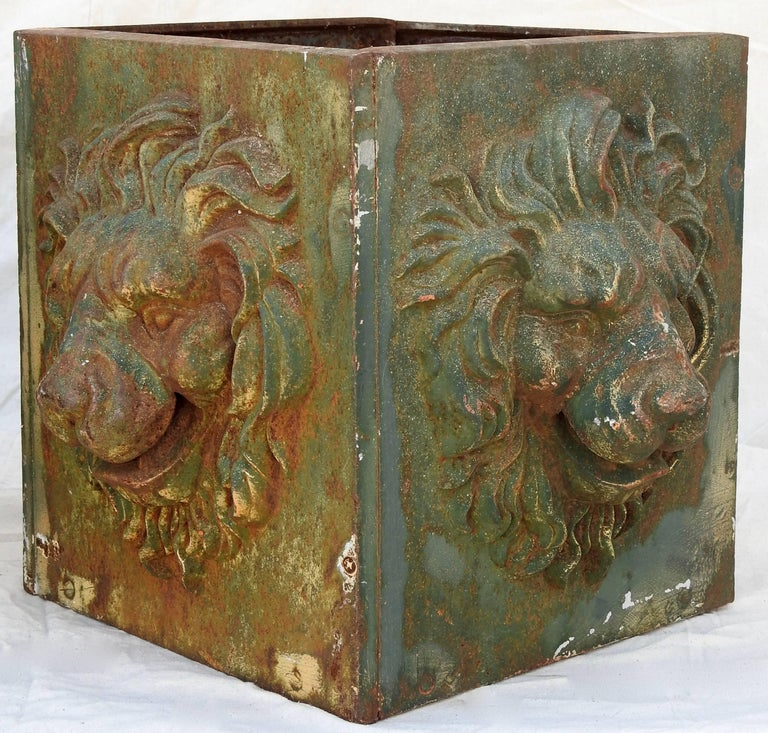 Featured is an exceptional pair of cast iron planter boxes. This pair of boxes have a dimensional lions face on each side. They are in the shape of a square box and have a greenish color with a rusty patina.
