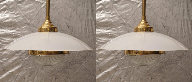 Pair of midcentury brass pendant lights with Lucite shade and textured glass lens. Takes a standard base light bulb and have been rewired for American use.