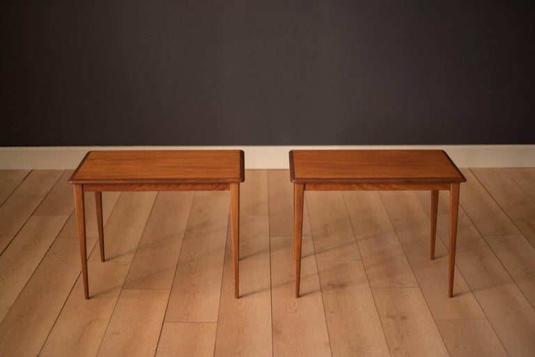 Vintage pair of side tables made in Sweden, circa 1960s. This set features tapered angled legs and teak table tops with contrasting solid afromasia edges.   Offered by Mid Century Maddist