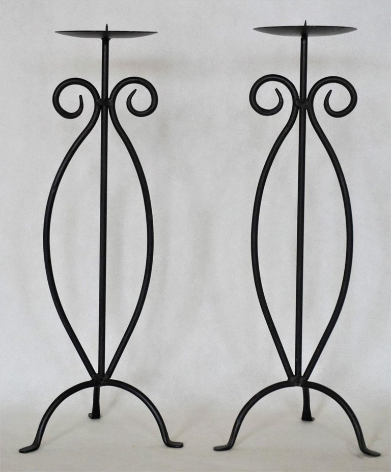 Pair of wrought iron candleholders rised on tripod base, black painted. Measures: Height 17.50 in (44.5 cm) Width/Depth 6.50 in (16.5 cm).