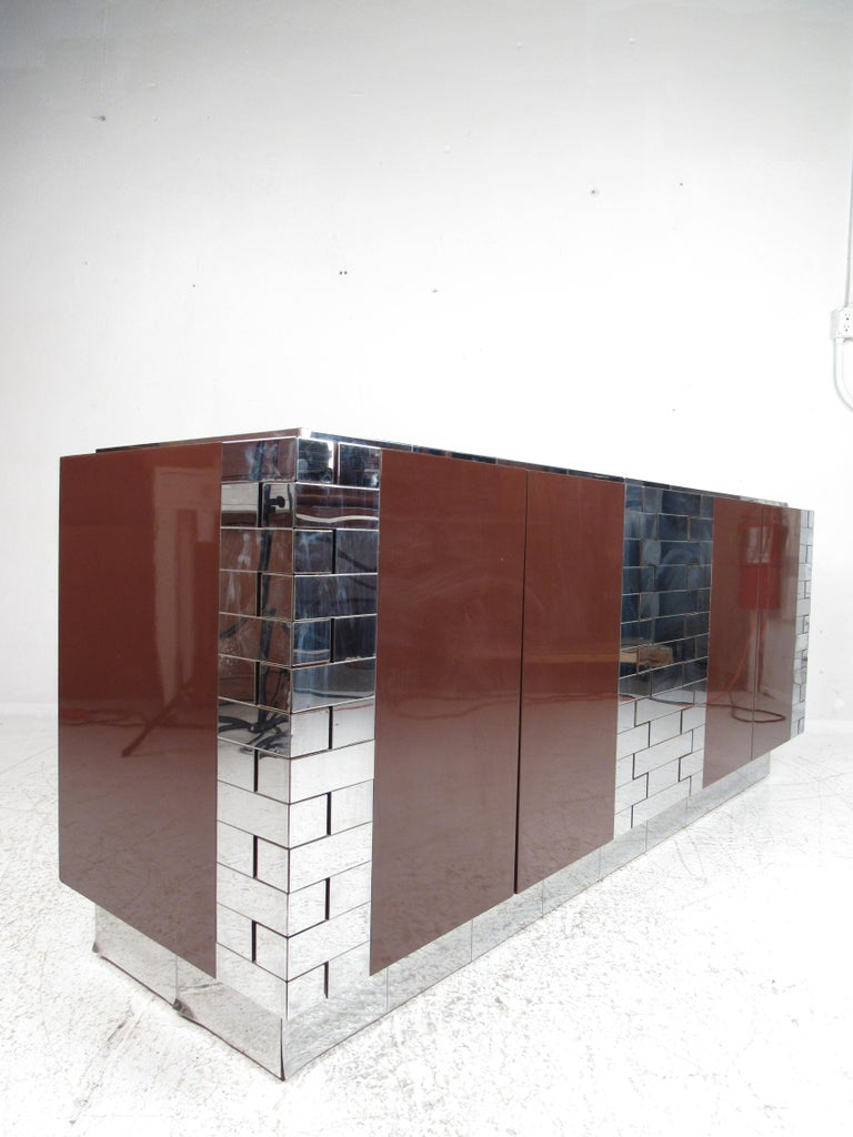 An iconic vintage modern design by Paul Evans with an elaborate chrome patchwork design. This stylish case piece boasts a spacious black interior hidden behind four cabinet doors. A two-tone design with a lacquered burgundy casing and unusual