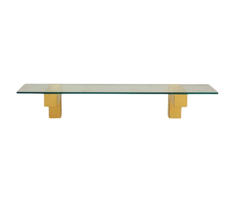 An incredible design, a cityscape wall shelf designed by Paul Evans in the 1970's. The set features fine heavy construction with brass clad patchwork design. Includes two L shaped wall brackets, and heavy clear glass shelf. Price includes the set as