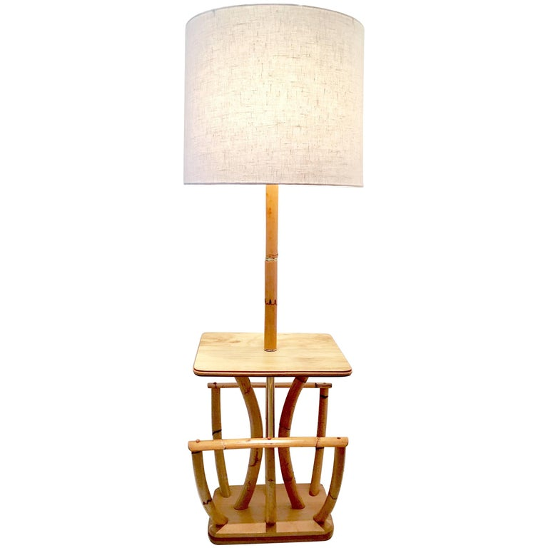 1930s Paul Frankl style rattan reed and brass floor table lamp with magazine rack. This unique and rare floor lamp features a center polished brass pole and ring detail with a large magazine rack and mahogany platform base. Includes brass finial and