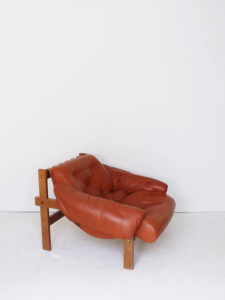 Stunning  leather armchair in manner of Brazilian designer Percival Lafer.  Featuring a solid wood frame with beautiful grain that supports the natural leather straps which the tufted  leather cushion rests on.  The original leather upholstery in