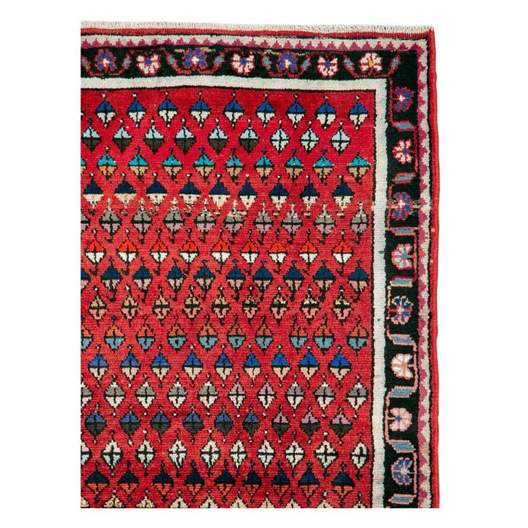 A vintage Persian Hamadan folk rug handmade during the mid-20th century in scatter/throw rug size with a red field filled with geometric botehs (paisleys).