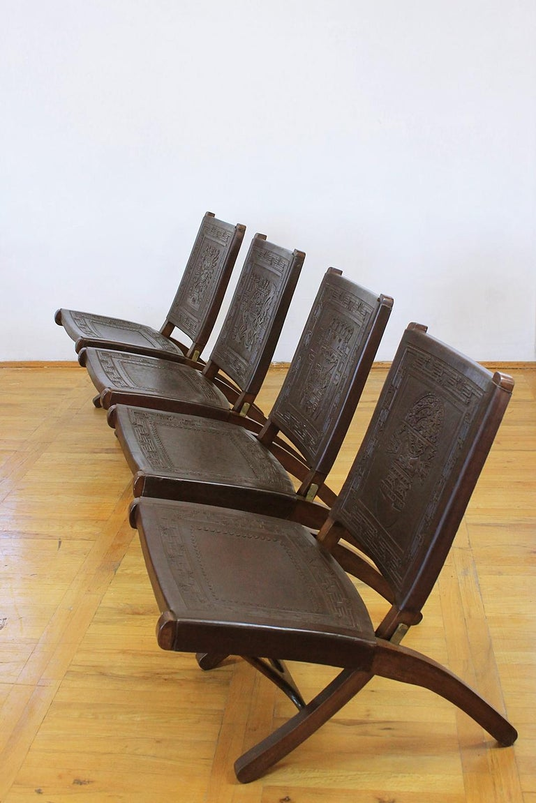 4 Peruvian leather hand tooled chairs:  4 Peruvian leather chairs having seat and each has a different Peruvian figure hand tooled into leather backrest. All on solid wood frame with brass folding mechanism.   Condition: Wear consistent with age