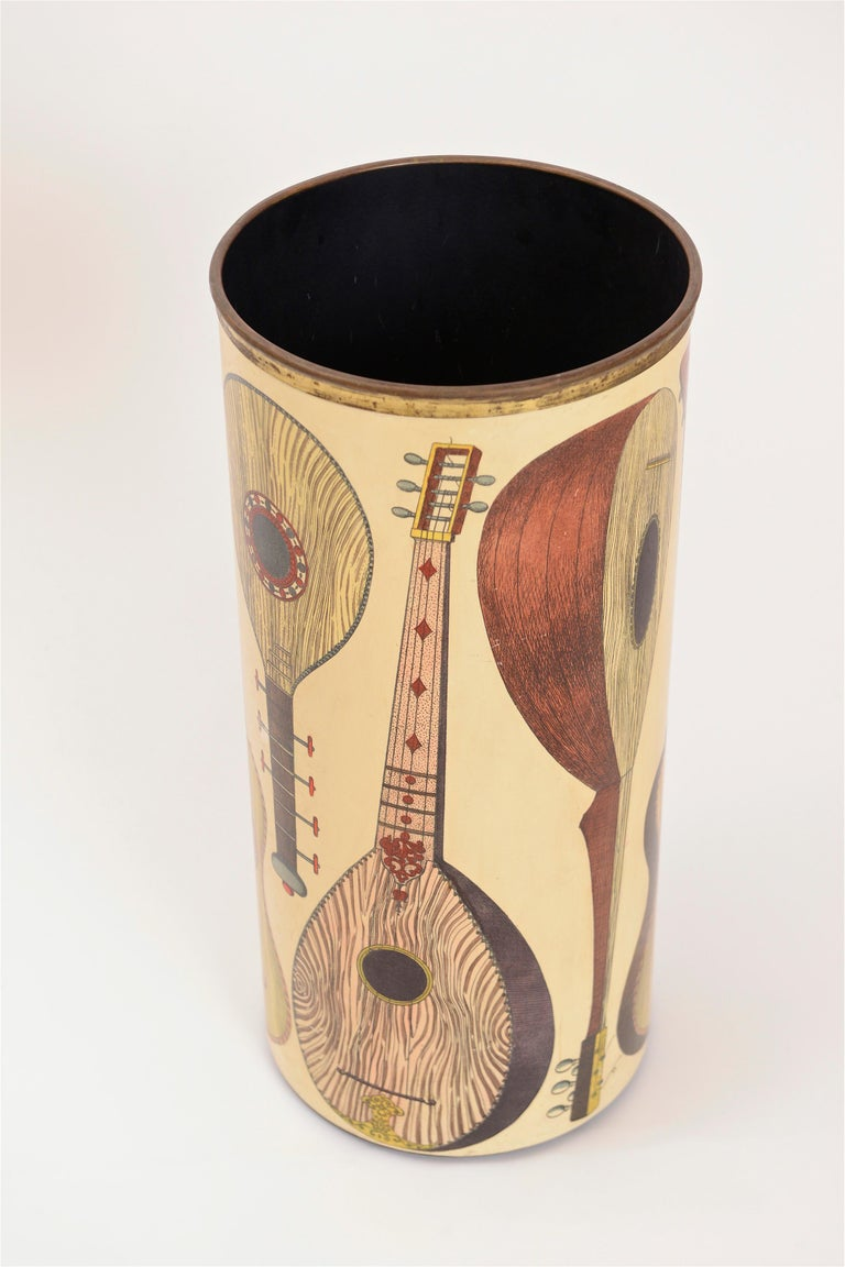 A beautiful umbrella stand from the 1950s by Piero Fornasetti. This 'instrumenti' model is decorated with eight lithographic transfers of different stringed instruments. In great condition, this umbrella stand is signed on the underside