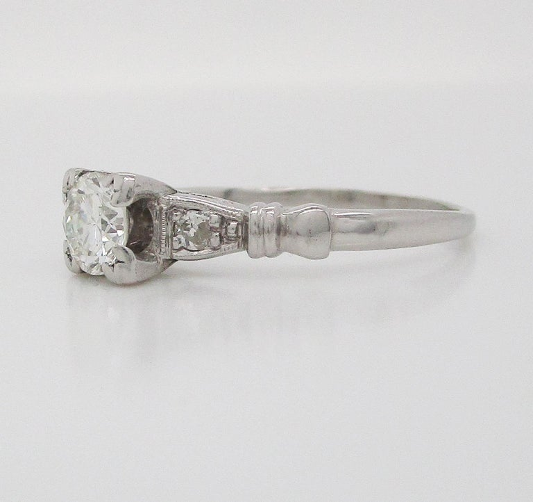 This is a stunning mid-century diamond engagement ring in platinum with lovely engraved shoulders. The ring features a diamond on each shoulder, framed by engraved details and accented by a fluted element on each shoulder. This ring is full of
