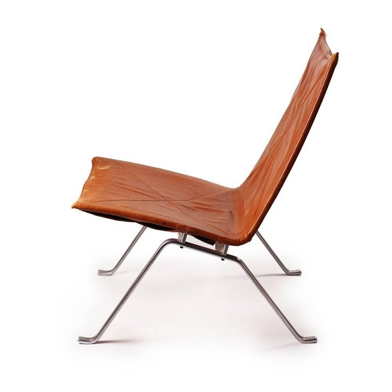 Original first edition PK 22 low chair designed 1956. Cognac leather seat on stamped polish steel frame. Poul Kjaerholme was one of the leading post war Scandinavian designers.