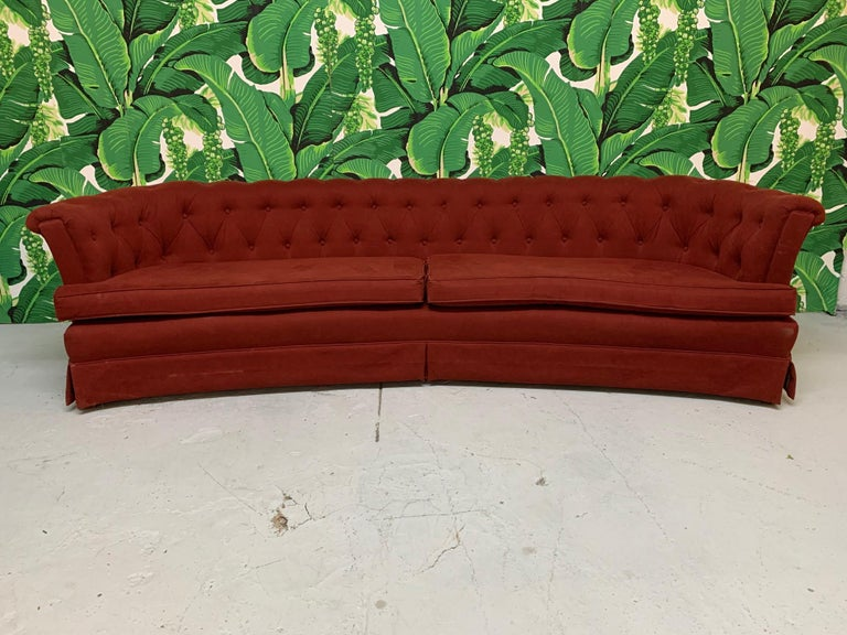 Large mid-century tufted sofa in the manner of Dorothy Draper features a curved shape and deep rich red velvet type upholstery.  Very good condition with no tears or holes and only very minor imperfections consistent with age.